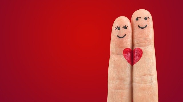 red background with two fingers up, decorated as people, with heart connecting them