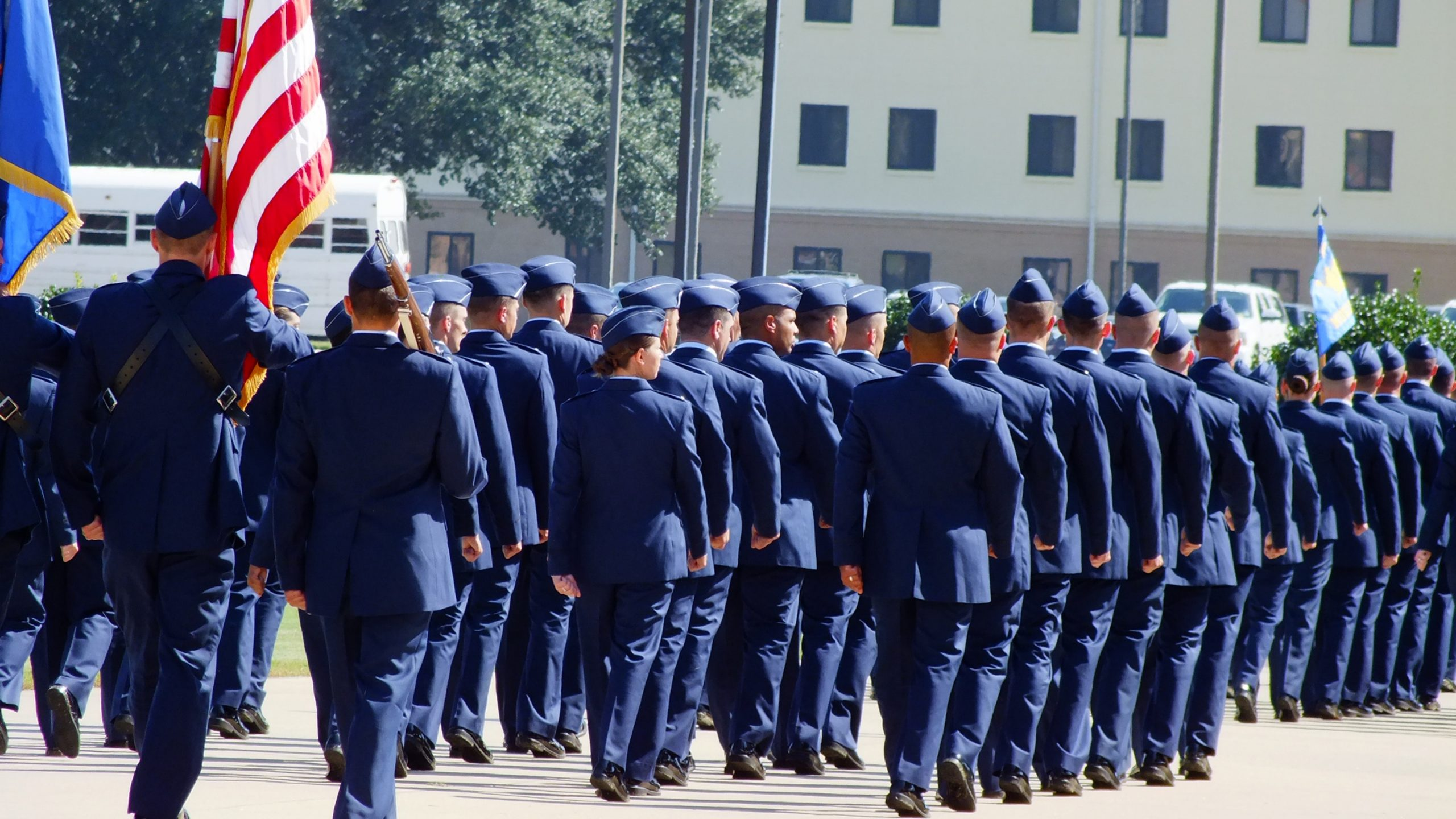 air force military airmen in blues marching with American flag
