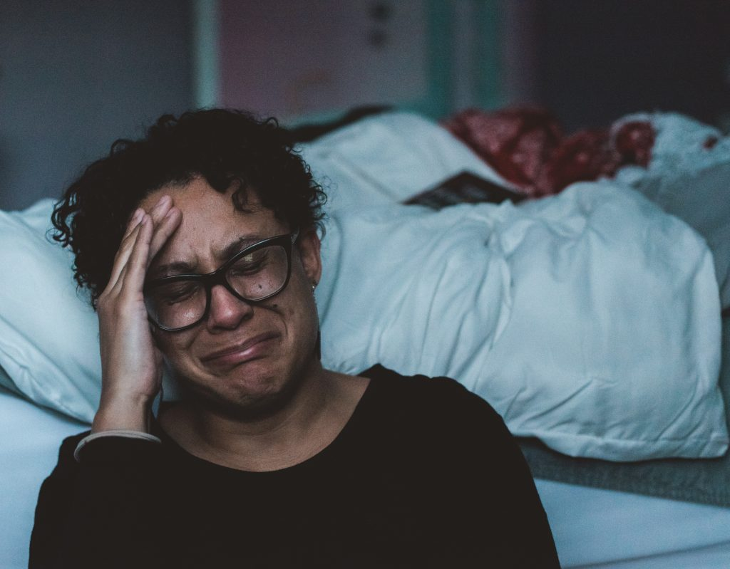 woman crying next to a bed in grief