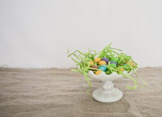 white platter with Easter grass and eggs on wood table