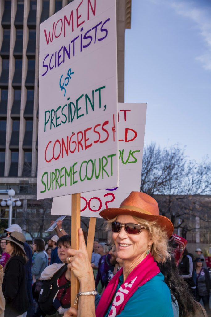 """woman in a march holding up a sign that states, """"women scientists for president, congress, supreme court"""""""