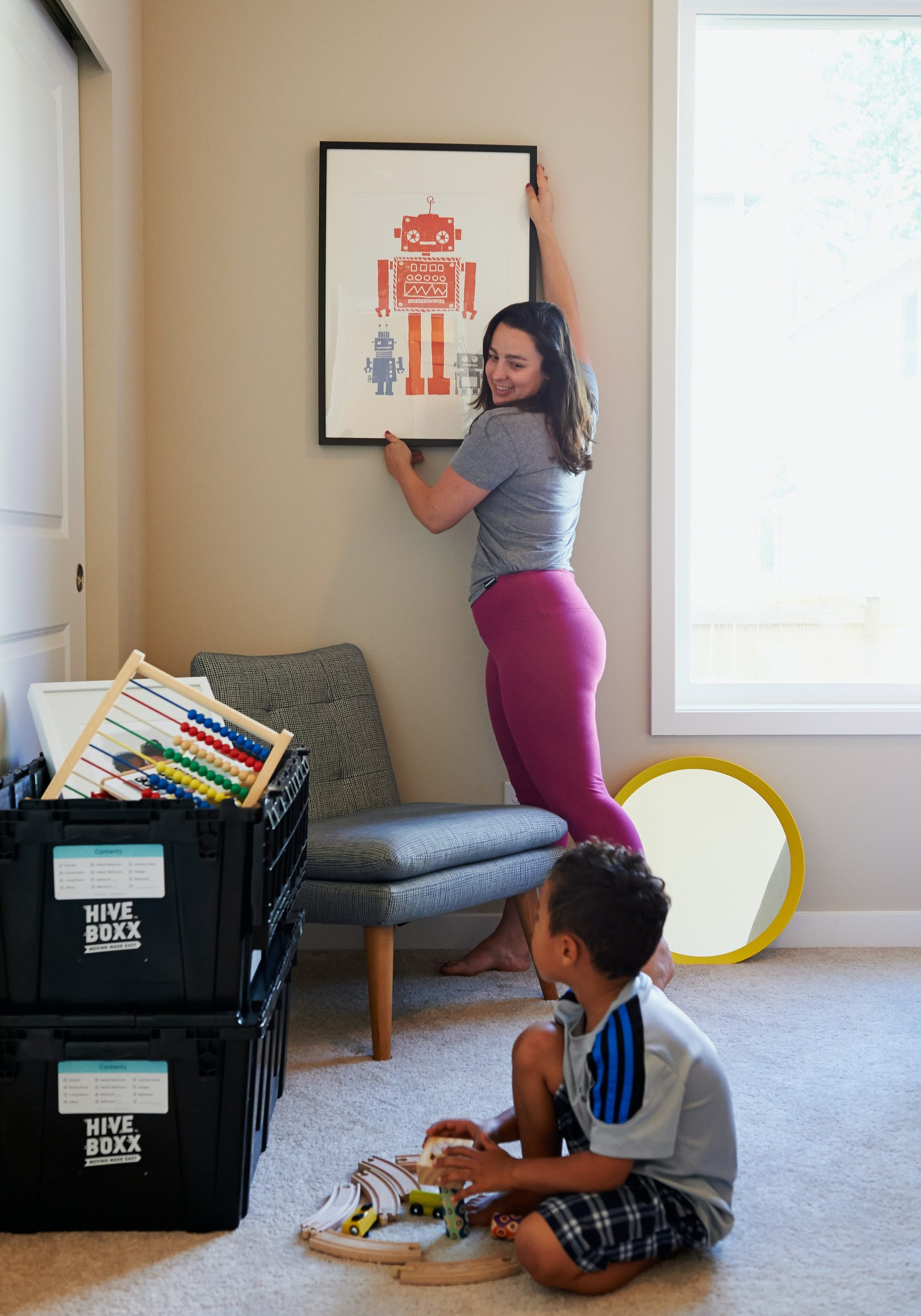 mother hanging a picture in a house with child watching