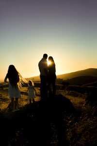 a family in a field backlit by the setting sun