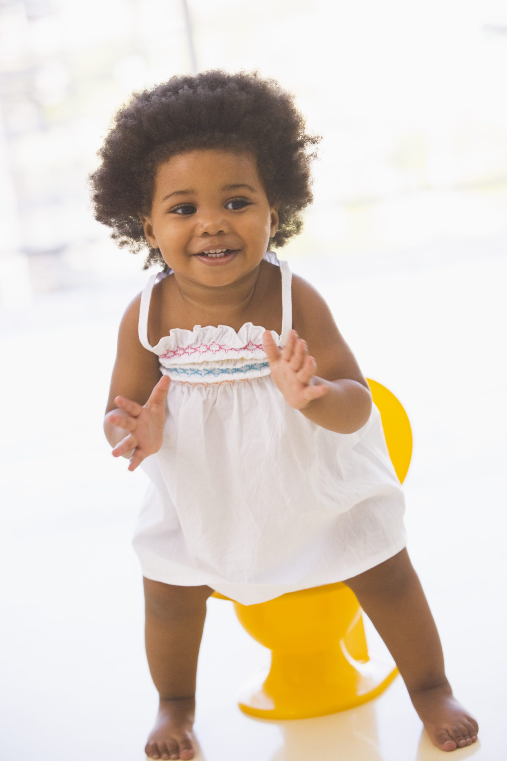 African-American girl smiling in front of a yellow potty training chair