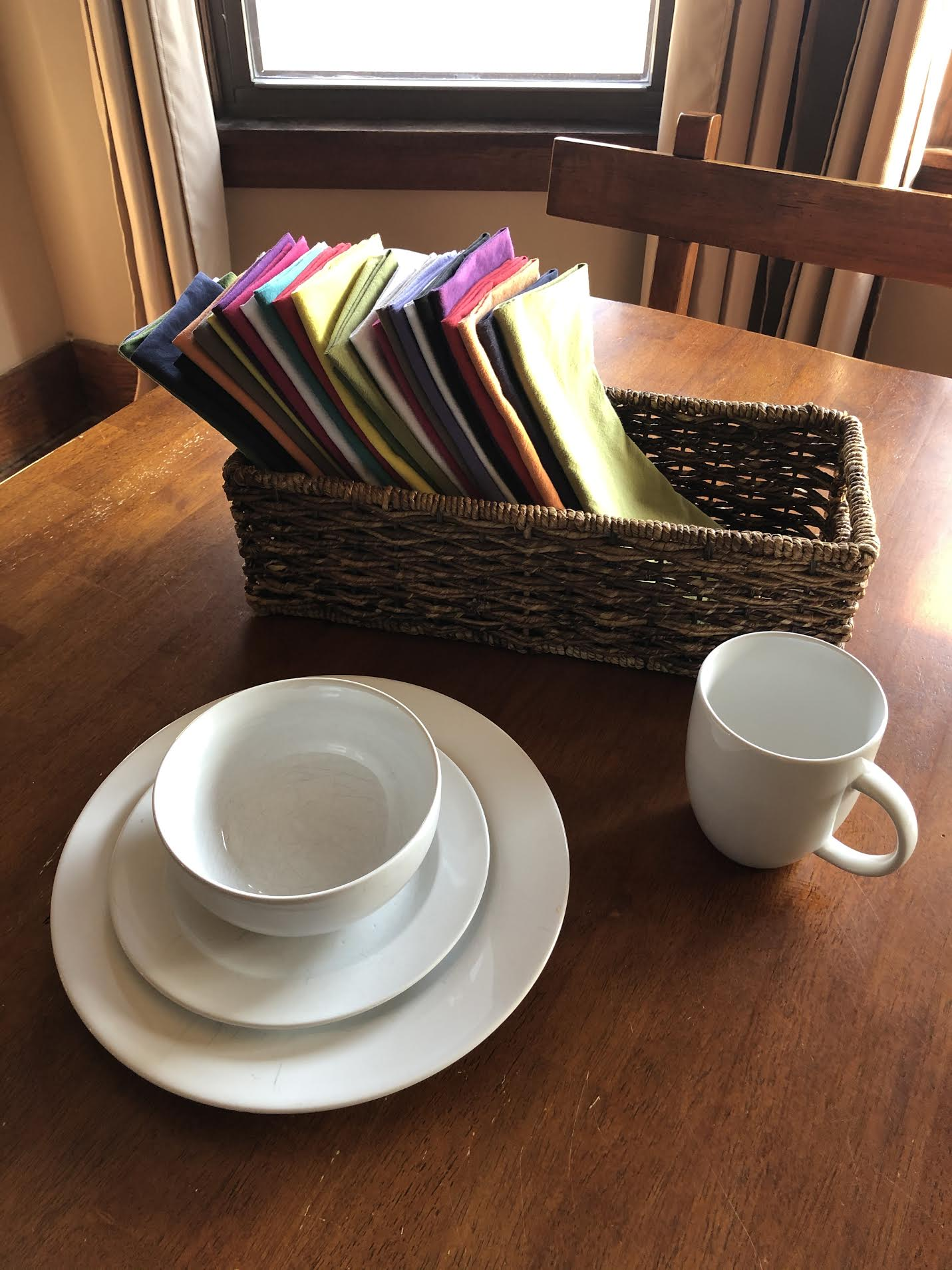 multicolored cloth napkins, white mug, white bowl, and white plate on a wooden kitchen table