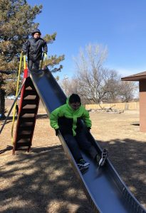 two kids one a playground slide