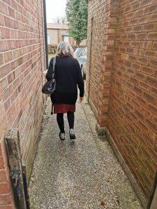 older woman walking down a brick alleyway