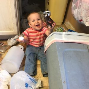 baby with an overturned garbage can