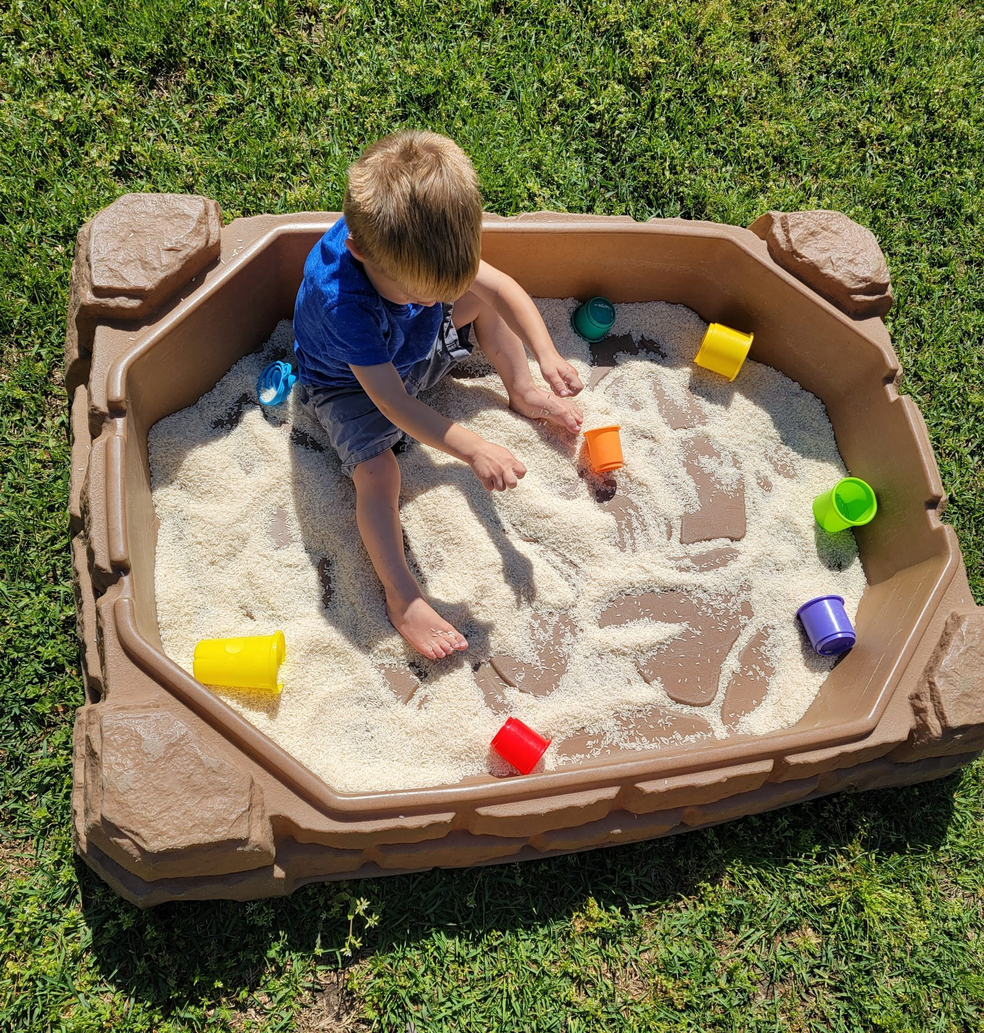 Little boy sitting in sand box playing with rice and colorful cups