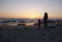 mom and daughter holding hands on a beach