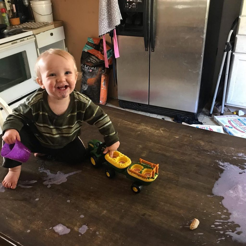 toddler on a table with spilled milk and toys