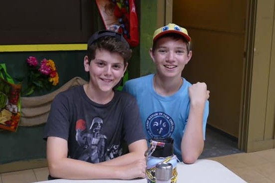 Two boys posing for a photo together at camp