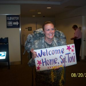 female service member in unifrom coming home from Iraq, smiling and holding a welcome home sign