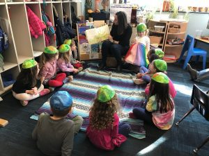 Children sitting in a circle listening to a parent reading a book