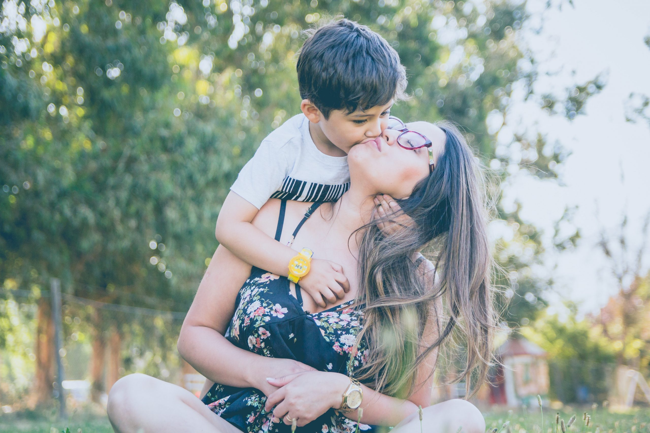 mother kissing son in a sunny field