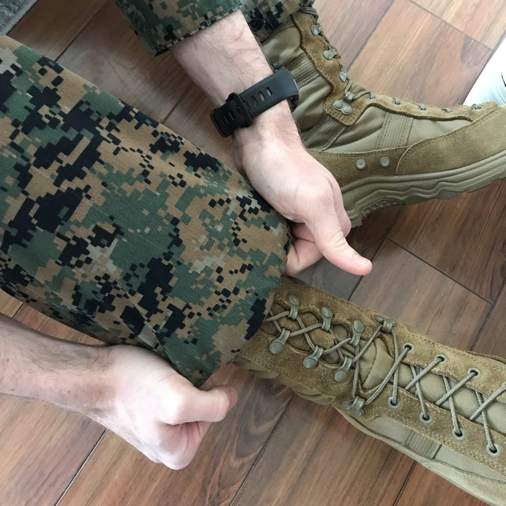two hands pulling down uniform pants over brown boots