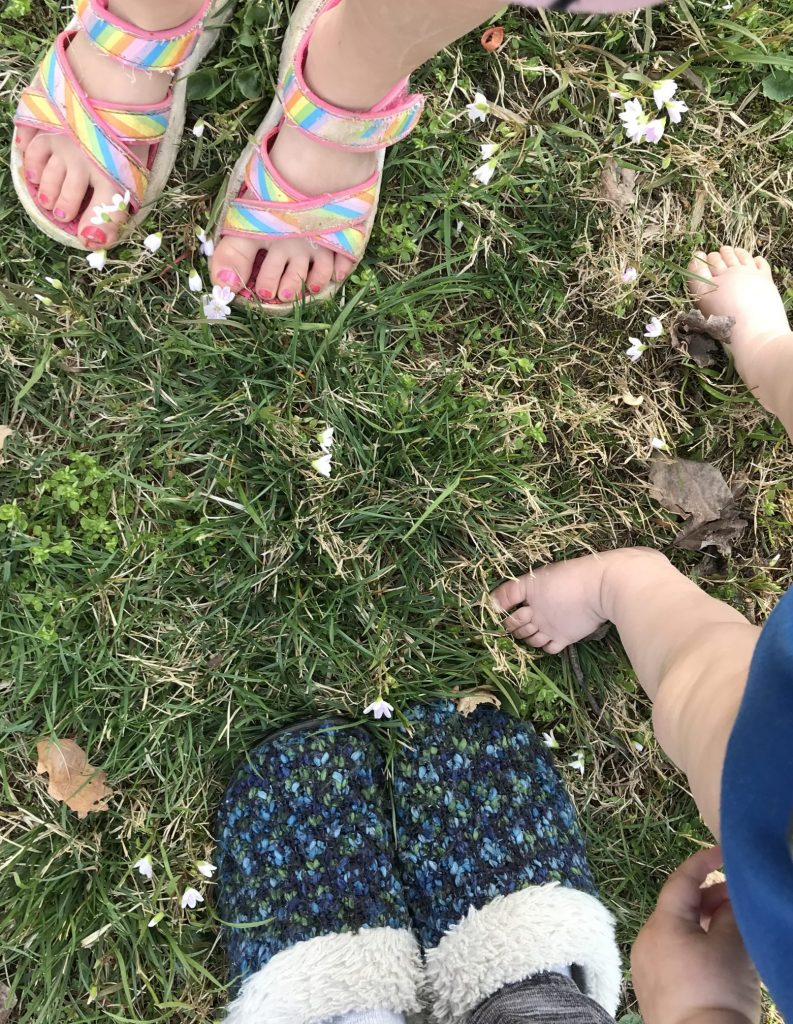 three pairs of feet: one small girls painted pink toes in rainbow sandals, baby toes in the middle, and a blue pair of slippers
