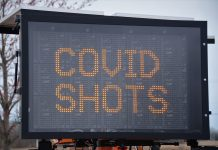 "large letter board with ""COVID SHOTS"" on screen"