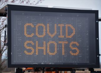 """large letter board with """"COVID SHOTS"""" on screen"""