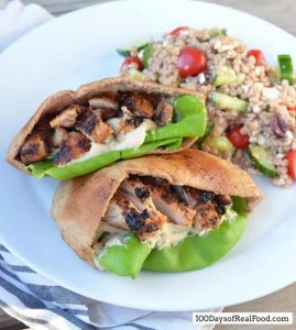 white plate with pita bread filled with grilled chicken and lettuce