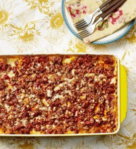 yellow and white tablecloth with a pan of lasagna, plate, 2 forks, and napkin