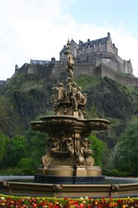 An ornate fountain is in the foreground surrounded by flowers. Edinburgh castle, Scotland, stands on a hill in the background.