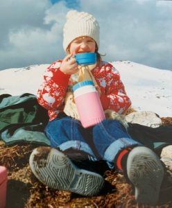 A girl sits on grass near a snowy mountain top in Scotland. She is wearing jeans and a red/white jumper and a white knitted hat. She is drinking from a pink and blue flask.