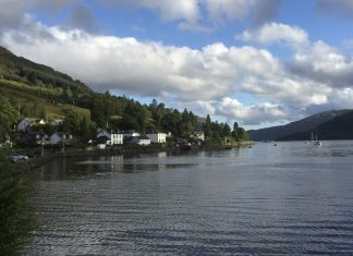 A coastal village in scotland sits on the banks of a loch. There are two sailing boats in the distance.