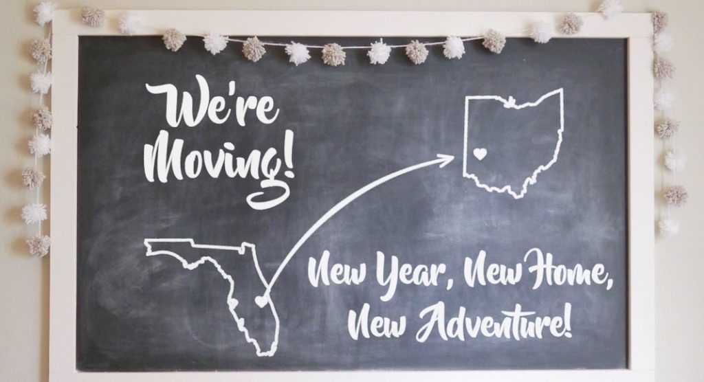 """chalkboard with """"we're moving! new year, new home, new adventure"""" written on it"""