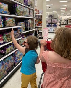 A girl in a peach dress is in the foreground with her back to the camera, she is pushing a red cart. There is a younger boy in front of her, also with his back to the camera, pointing and lego sets on a shelf.