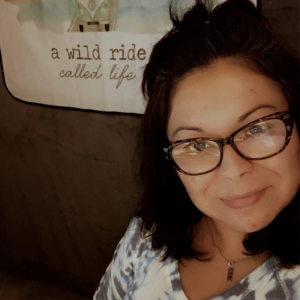 """Annette Whittenberger in her studio with """"A wild ride called life"""" banner"""