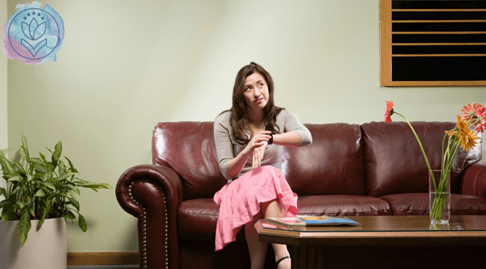 woman sitting on a couch looking at watch and waiting