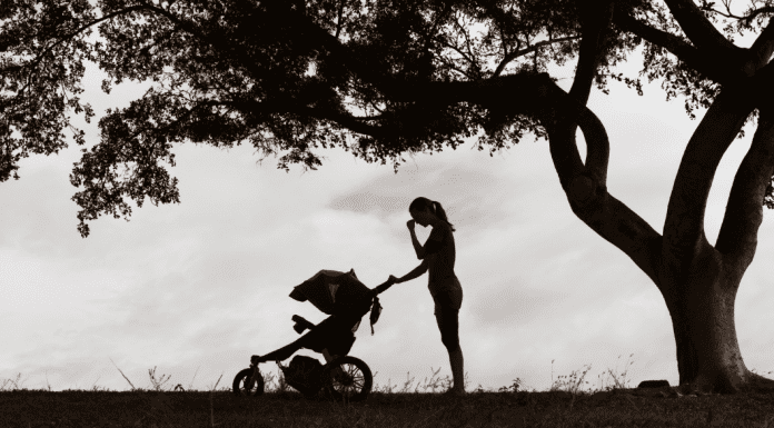 woman with a stroller outside in black and white