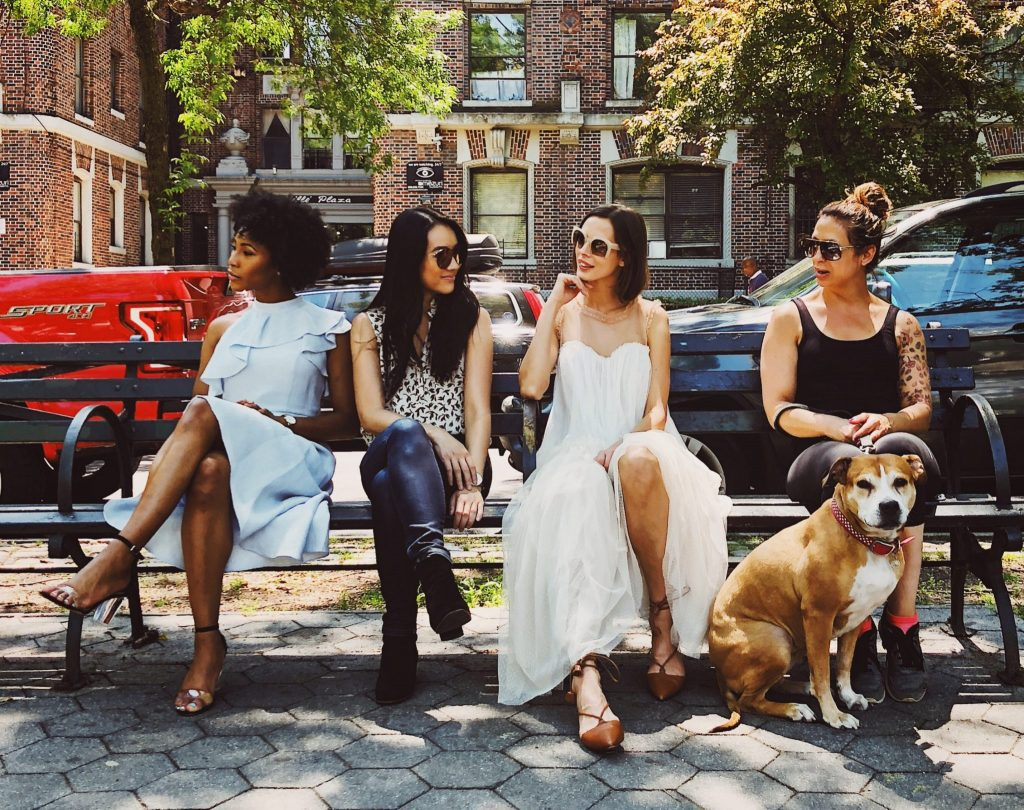 a group of women sitting on a bench with a dog in a city
