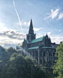 A large, dark, gothic style building sits amongst green trees. It has a green room and a spire reaches into the blue sky above.