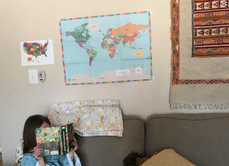 child in blue dress sitting on couch reading a book with maps behind her on the wall
