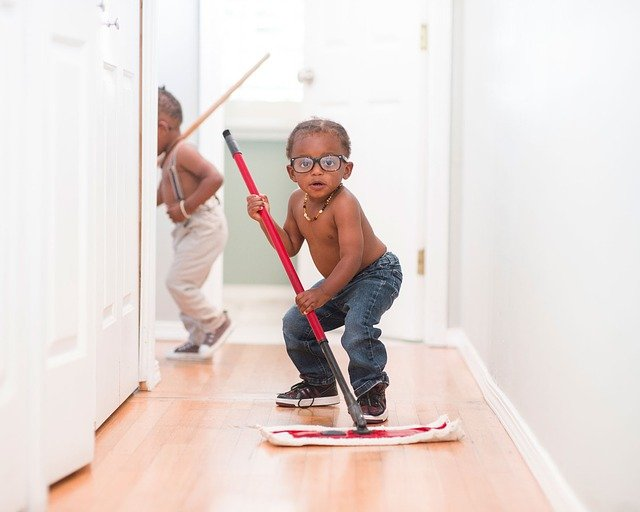 Two young boys mopping a wood floor in a house