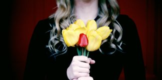 woman holding a bouquet of flowers in black to signify mourning