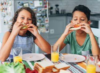 two children sitting at a table and eating sandwiches
