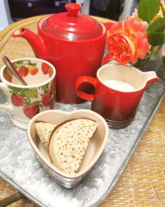 red teapot with tea cups and small sandwiches