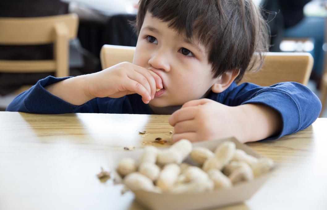 small boy eating peanuts at a table