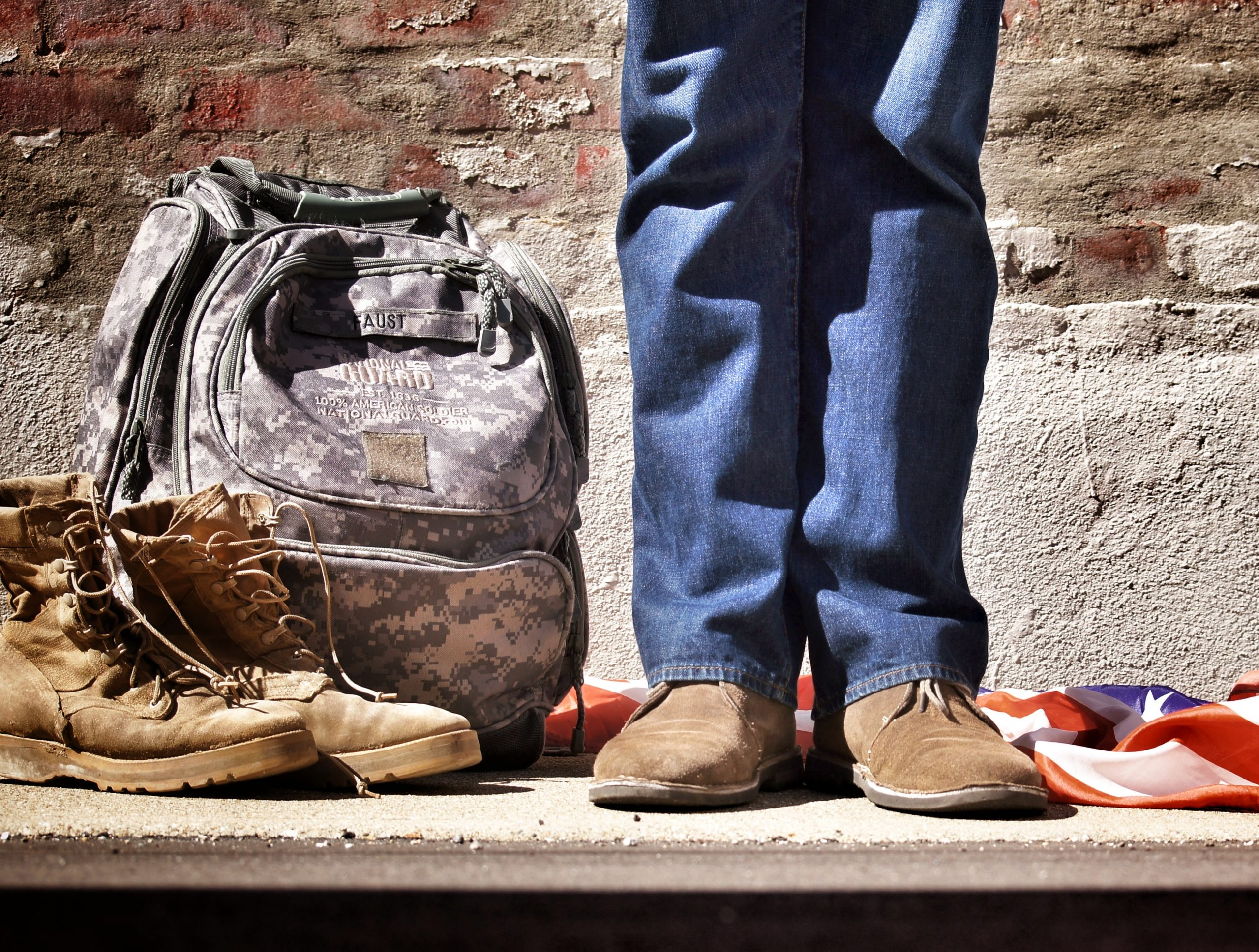 boots, camo bag, and flag on the ground with feet