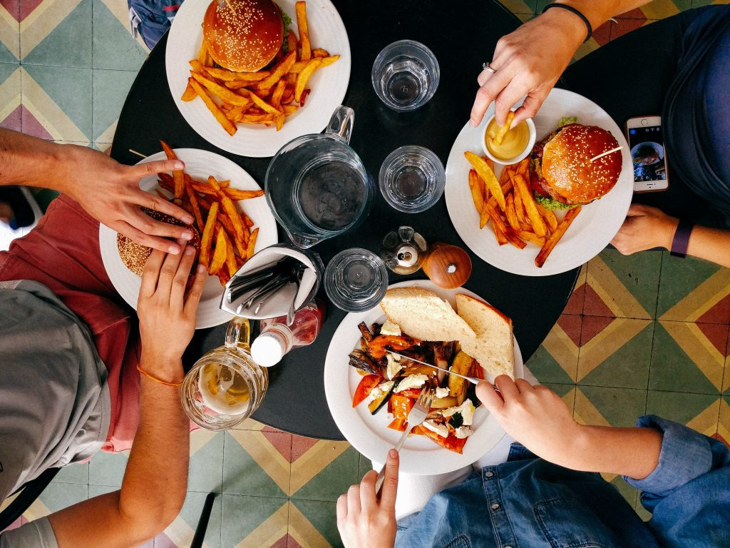 four people eating at table with various foods