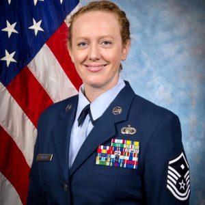 Female Veteran, Sarah Loicano, in AF uniform smiling in front of a flag.