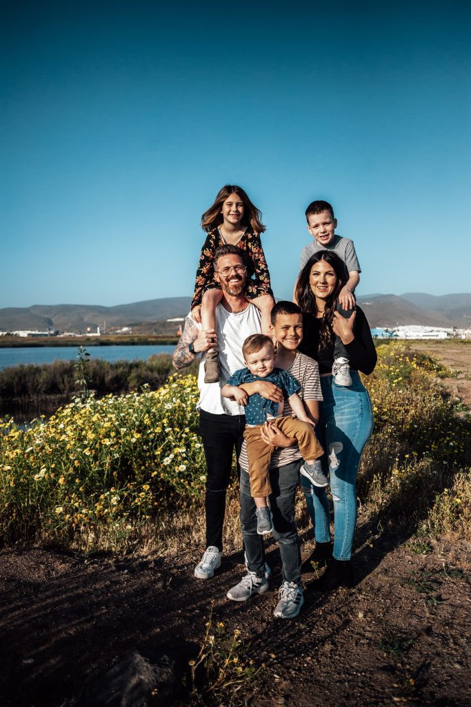 large family standing near the water