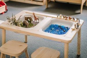 sensory table with water beads, sand, and small toys