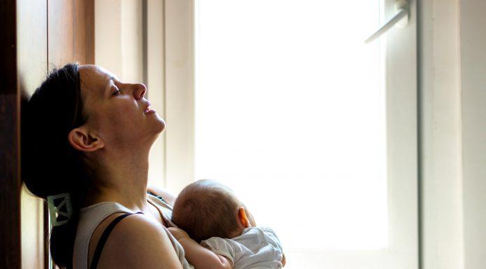 Woman holding infant appearing tired, concerned, sad, depressed
