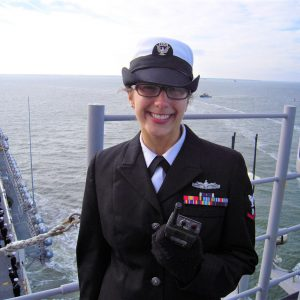 Female sailor in unifrom smiling on a ship in the ocean