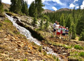 family standing next to a waterfall in the mountains