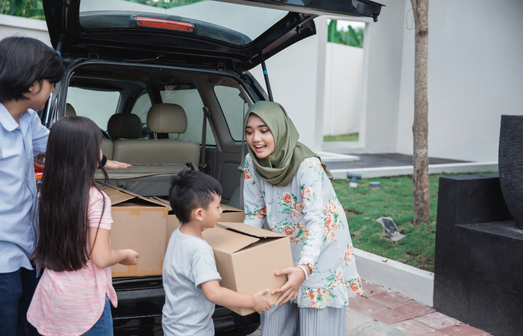 woman in hijab with children unloading moving boxes from a car